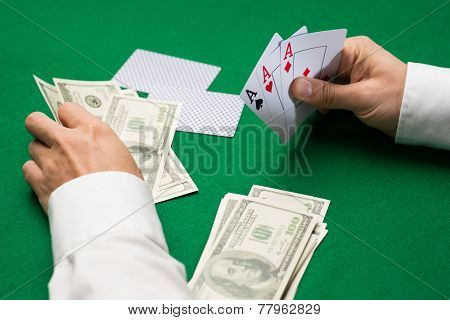 casino, gambling, poker, people and entertainment concept - close up of poker player with money holding playing cards at green casino table