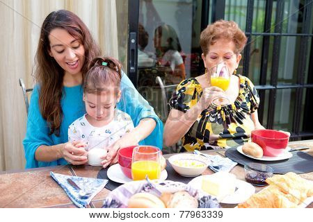 Beautiful hispanic family having breakfast together on the outdoor dining showing family bonding time. Focus is on child learning to drink milk.