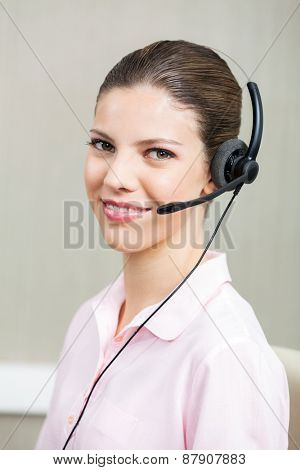 Closeup portrait of smiling female call center employee using headphones at office