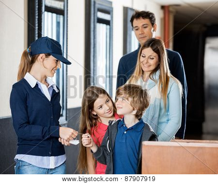 Female worker checking movie tickets of family at cinema