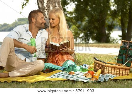 Romantic couple at marriage anniversary picnic. Casual blonde caucasian woman reading book and handsome man with glass.