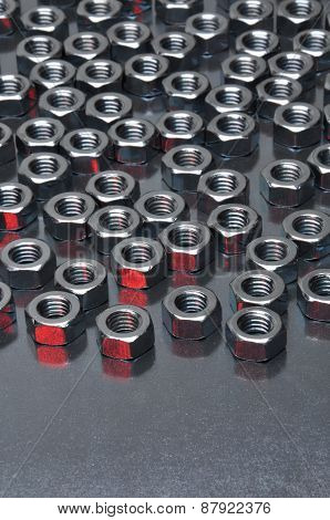 Shiny metal nuts on a metal surface