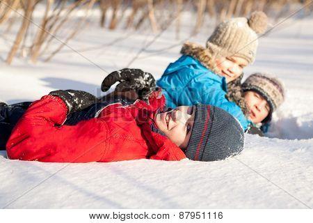 Children In Winterwear Playing In Snowdrift