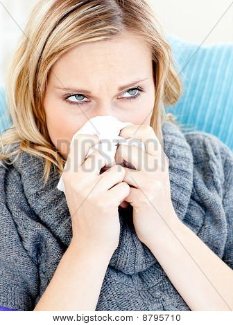Dejected Woman Lying On A Sofa With Tissues And Blowing