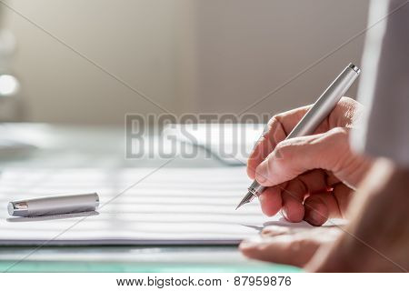 Businessman Writing On A Document