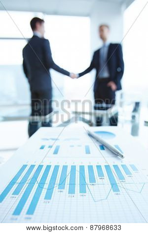 Business document with chart and graph on workplace with two men handshaking on background