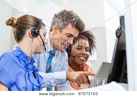 Manager with customer service executives using tablet computer in office