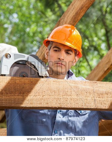 Male construction worker using electric saw on timber frame at site