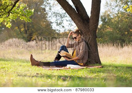 Woman Reading A Book Under The Tree At Daytime