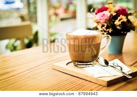 cappucino coffee on wood table and flowers in a vasemade vintage style.