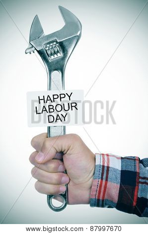 closeup of the hand of a young caucasian worker man with an adjustable wrench and a signboard with the text happy labour day written in it