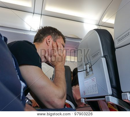Man Feeling Headache While Sitting At His Seat In Airplane