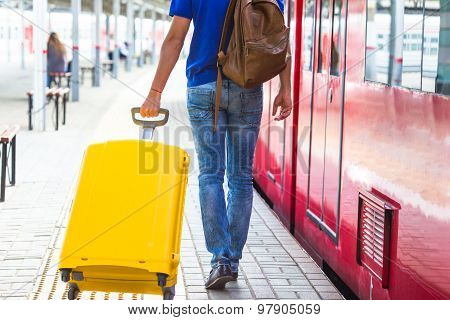 Back view of man with luggage at a train station