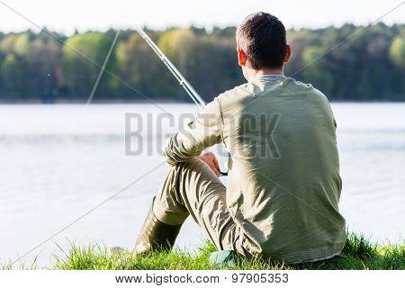 Angler sitting in grass at lake fishing with his rod, a very peaceful scene