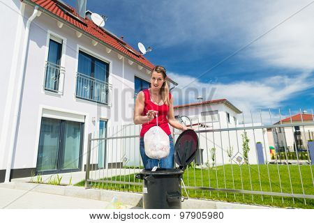 Woman throwing the garbage away in container