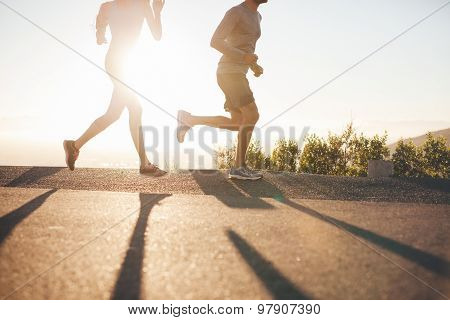 Two People Running On Country Road At Sunrise