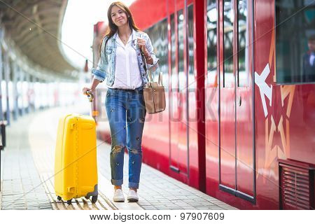 Young woman with luggage at a train station waiting for express train