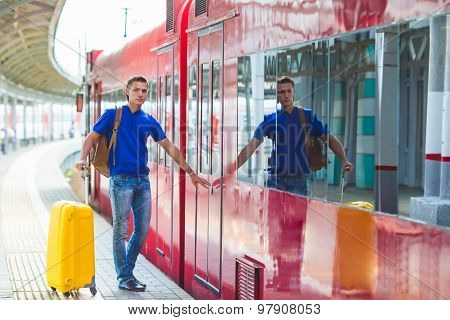 Young man with baggage at a train station near Aeroexpress