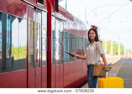 Young caucasian girl with luggage at station traveling by train