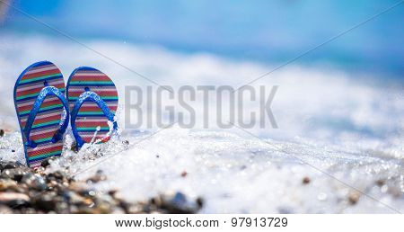 Blue flip flops on beach in front of the sea