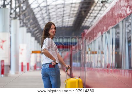 Young happy woman with yellow luggage at a train station