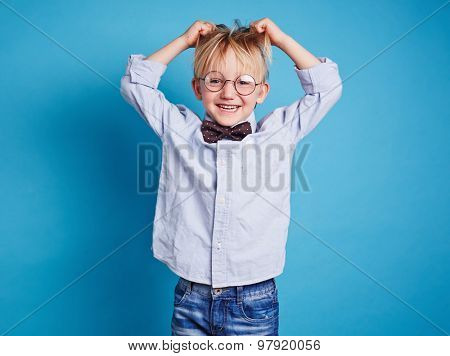 Little boy in eyeglasses and bowtie tousling his hair