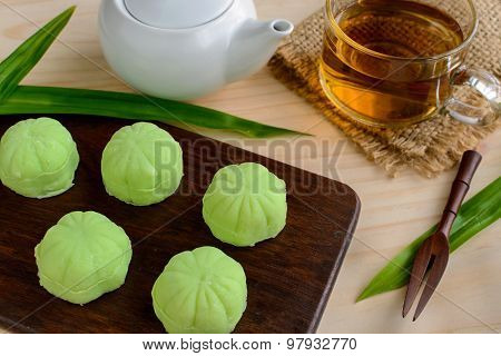 Greentea mochi flavored with bean filling and cup of tea on wooden table poster