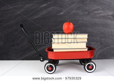 A red wagon full of school books with an apple on top. horizontal format in front of an out of focus chalkboard. Back to School concept with copy space.
