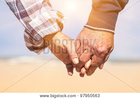 Senior Couple In Love Walking At The Beach Holding Hands In A Romantic Sunny Day - Concept Of Love