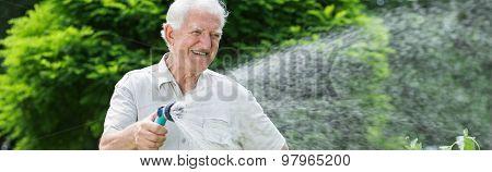 Happy Gardener Using Garden Hose