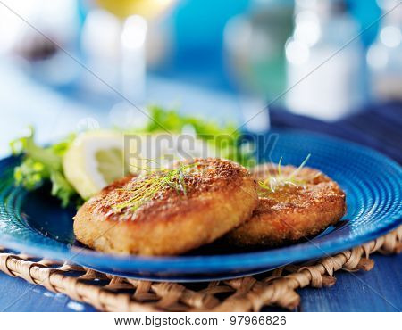 plate with two golden fried Maryland crab-cakes with dill garnish