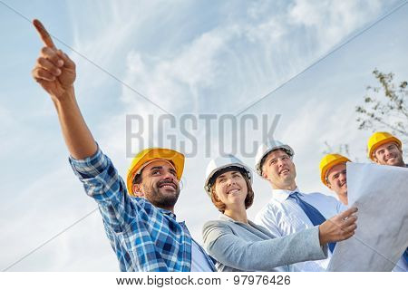 business, building, teamwork and people concept - group of builders and architects in hardhats with blueprint on construction site