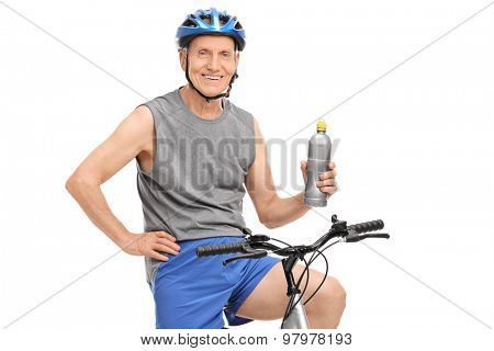Senior man with a blue helmet holding a water bottle and posing seated on his bike isolated on white background