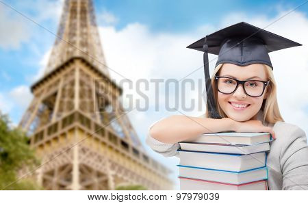 education, school, knowledge and people concept - picture of happy student girl or woman in trencher cap with stack of books over paris eiffel tower background
