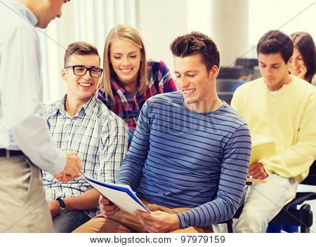 education, high school, teamwork and people concept - group of smiling students with notebooks and teacher talking in classroom