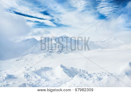 Winter Snow-covered Mountains And Blue Sky With White Clouds
