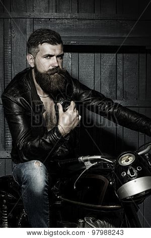 Handsome brutal unshaven sexual male biker in black leather jacket jeans with sun glasses sitting in garage on motor bike looking forward on wooden background vertical picture poster