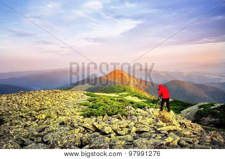 Photographer taking pictures on a hill mountaintop