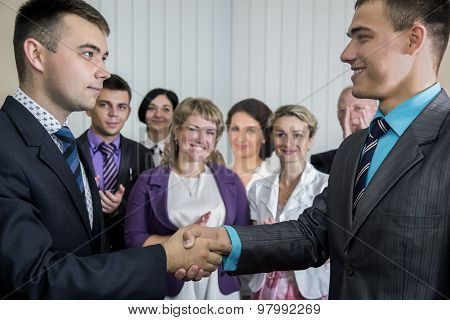 Two young businessmen congratulates each other
