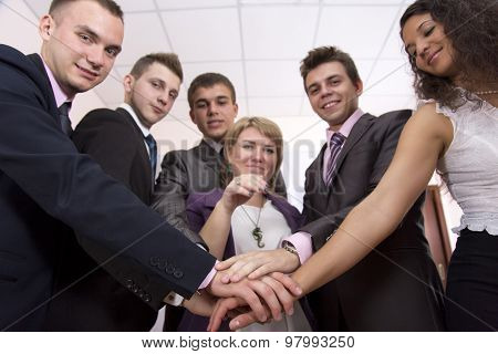 Friendly harmonious business team Six business people join hands and smiling. Focus is on hands, but face expression is recognisable poster