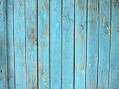 Old wooden planks standing upright with a shabby blue paint all over the field image for use as background or wallpaper poster