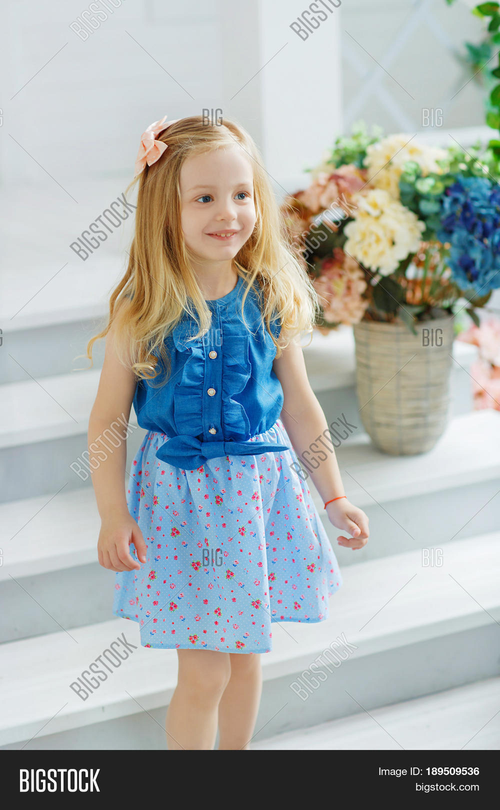 a64ef9f1375a A little girl in a blue shirt and a patterned skirt happily meets her  friends at