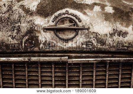 BERLIN - MAY 13 2017: Dirty and rusty hood emblem of Opel (Olympia) Rekord Caravan. Sepia. Exhibition