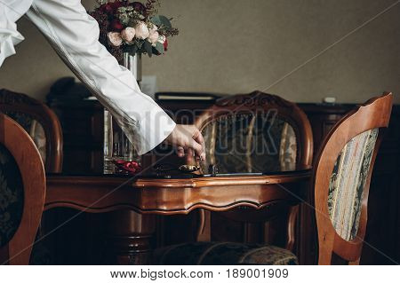 Groom Getting Ready In The Morning Before Wedding Ceremony, Holding Cuff Links In Hand In Rich Room