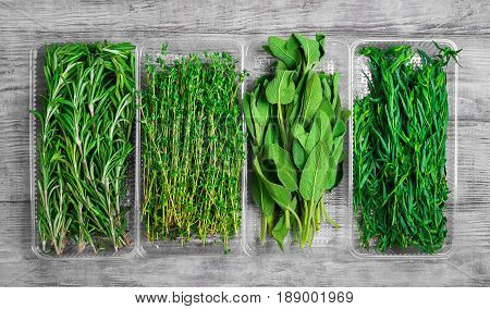 Assortment of fresh herbs for meat and fish tarragon parsley rosemary thyme sage. Light white wooden background. Top view.