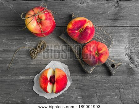 Flat doughnut peaches (Saturn peach) with hemp rope on gray wooden table and board. Flat doughnut peach cut into two halves. Top view.