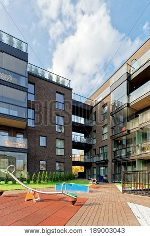 Vilnius, Lithuania - September 30, 3016: Children playground and Modern architecture of apartment building. And outdoor facilities.