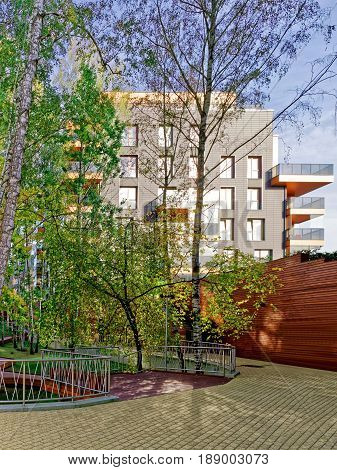 Vilnius, Lithuania - September 30, 3016: Birch trees and Modern glass residential building. And outdoor facilities.