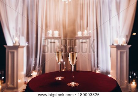 Glasses With Bubble Champagne On Red Table At Evening Wedding Ceremony Reception, With Lights In Gar