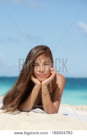 Beautiful portrait of young brunette mixed race Asian Caucasian woman on beach with sepia vintage filter. Serene looking model with healthy long brown hair relaxing lying on beach on vacation.